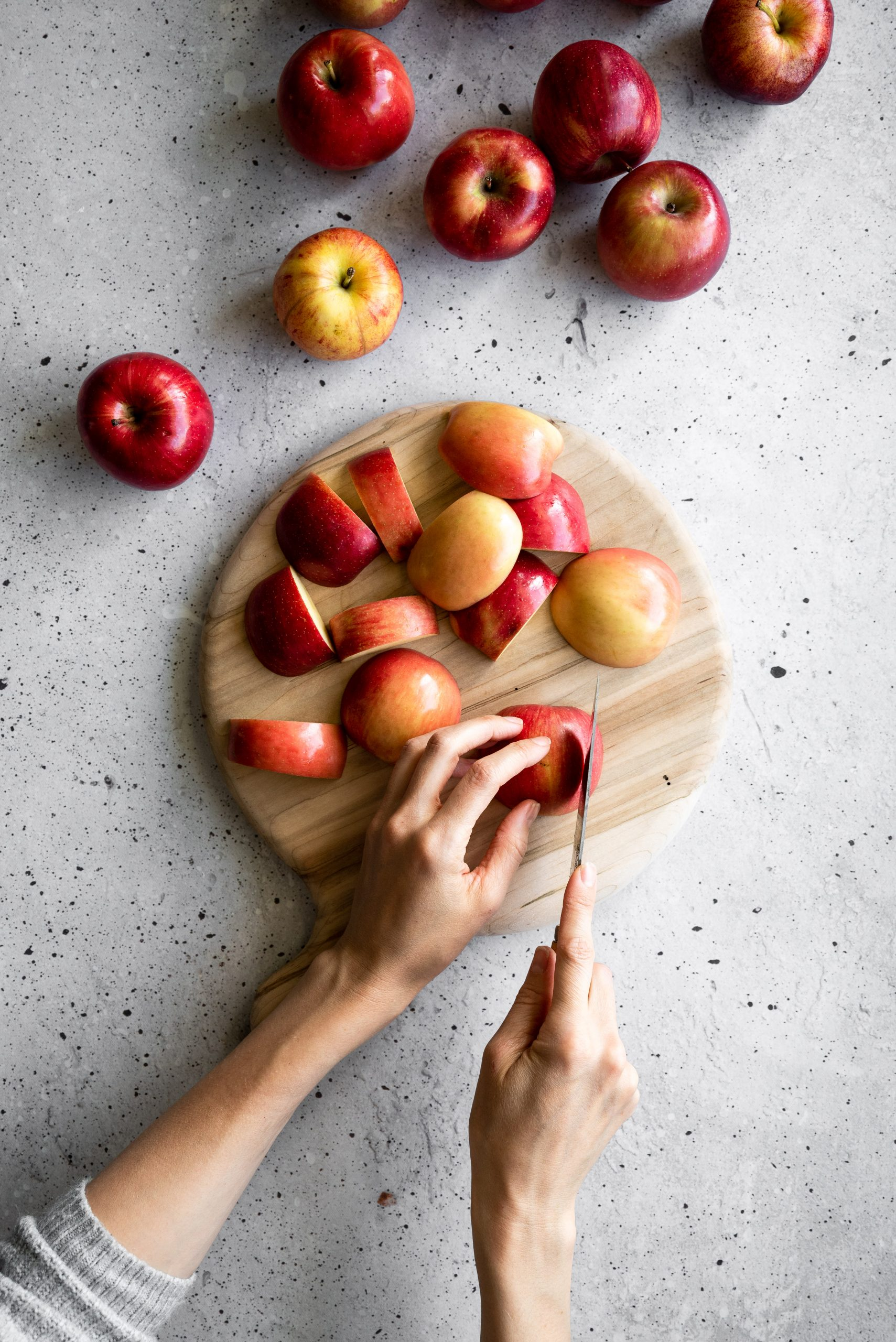 overhead image of a person slicing apples on a cutting board.