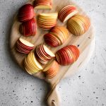 overhead image of several sliced apple section on a cutting board.
