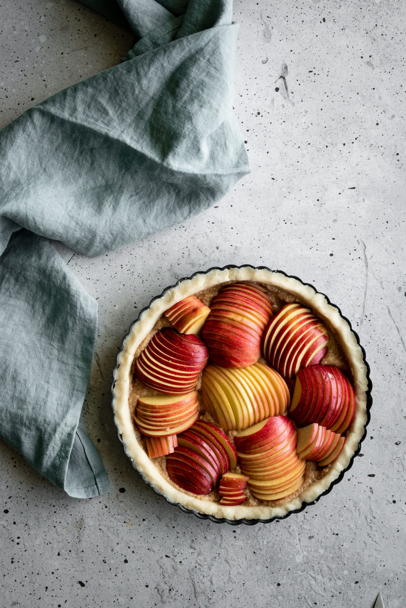 overhead image of an unbaked apple tart with a blue linen on the left.