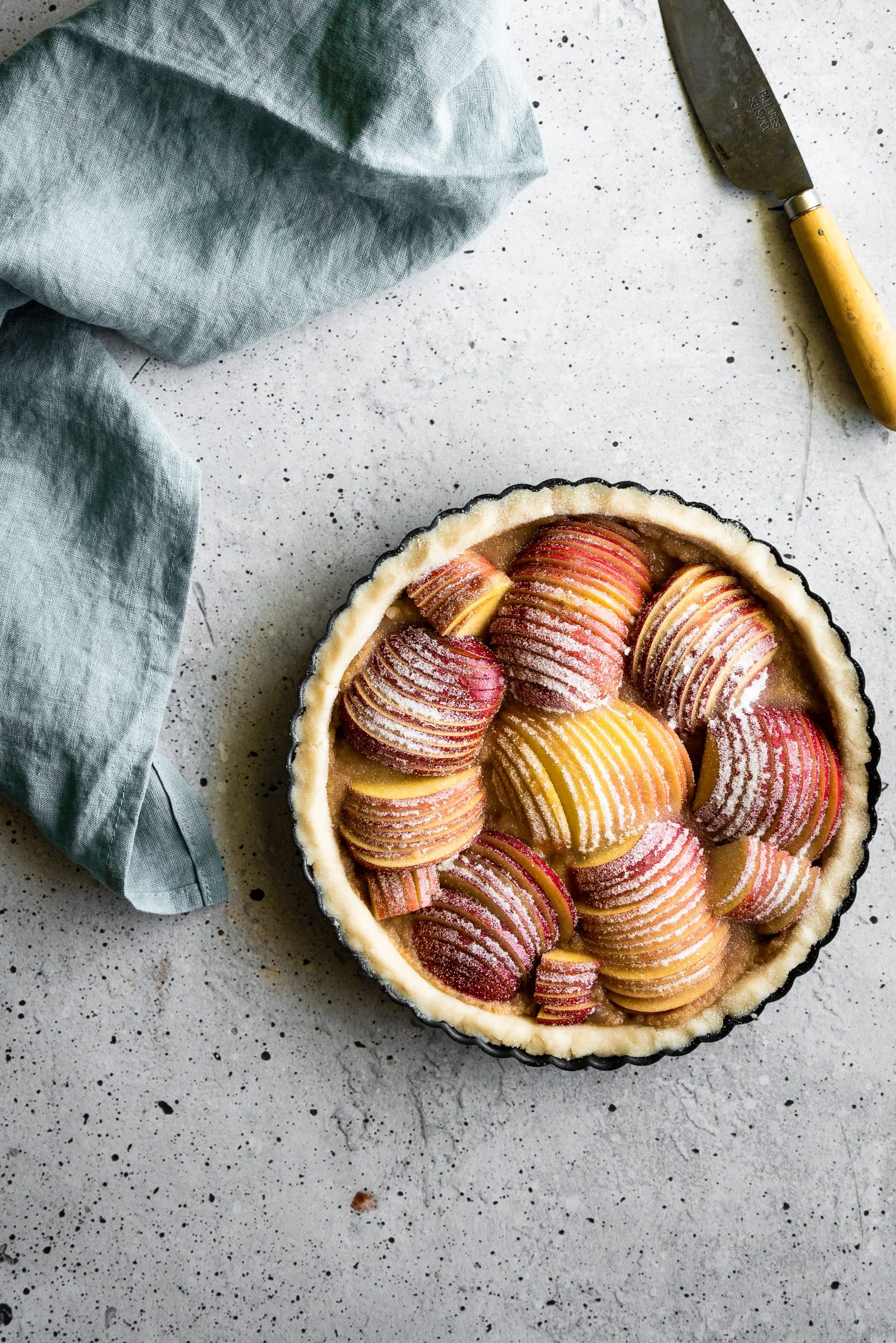 overhrad image of an unbaked apple tart with a blue linen on the left and a paring knife on the upper right.