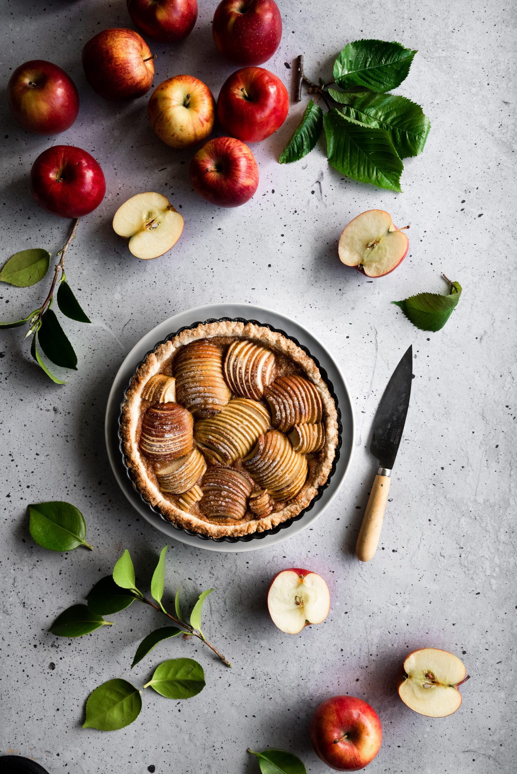 overhead image of a french apple tart on a wire rack surrounded by apples, leaves and a paring knife.
