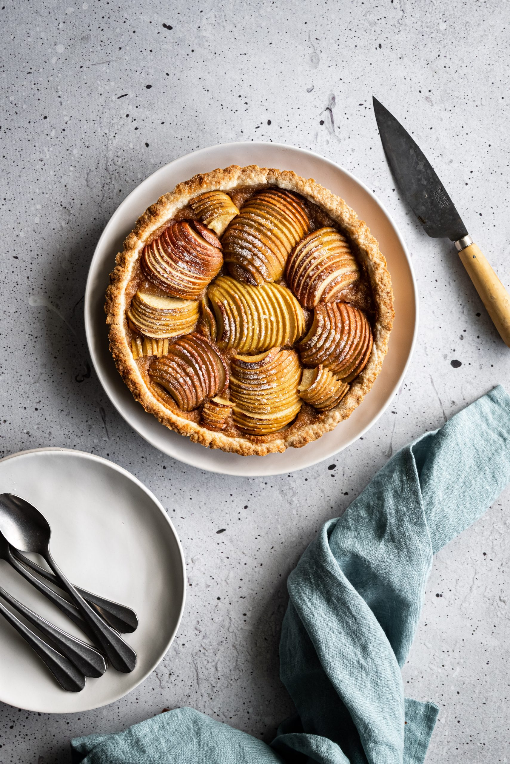 overhead image of a french apple tart on a grey surface with white dishes, a blue linen and a paring knife.