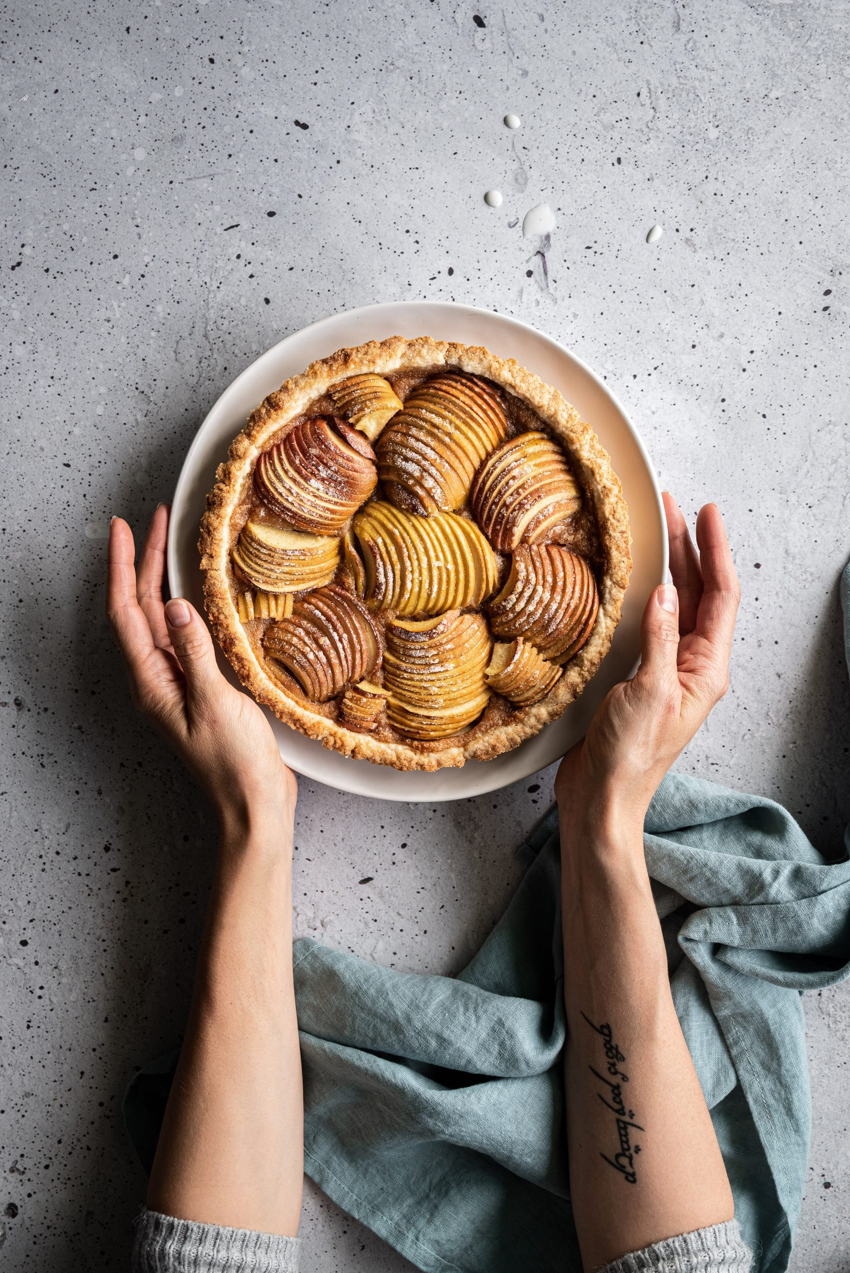 overhead image of a vegan french apple tart on a grey surface with two hands holding the tart and a blue linen on the bottom right.