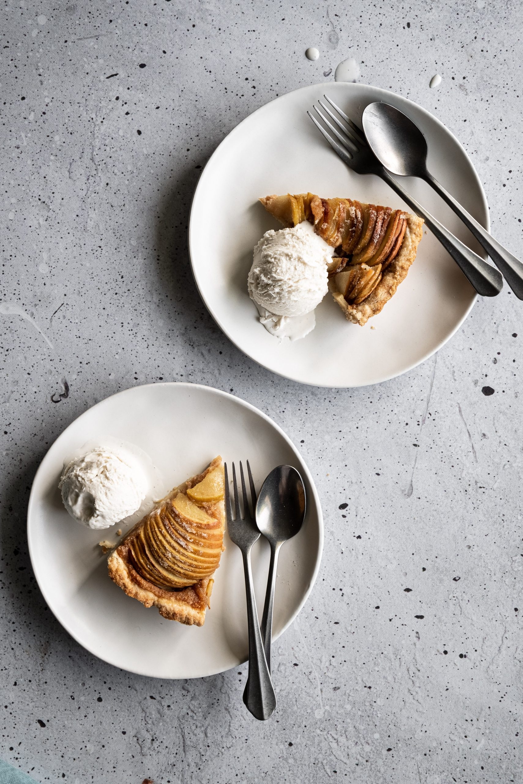 overhead image of two white plates with apple tart slices, ice cream and cutlery.