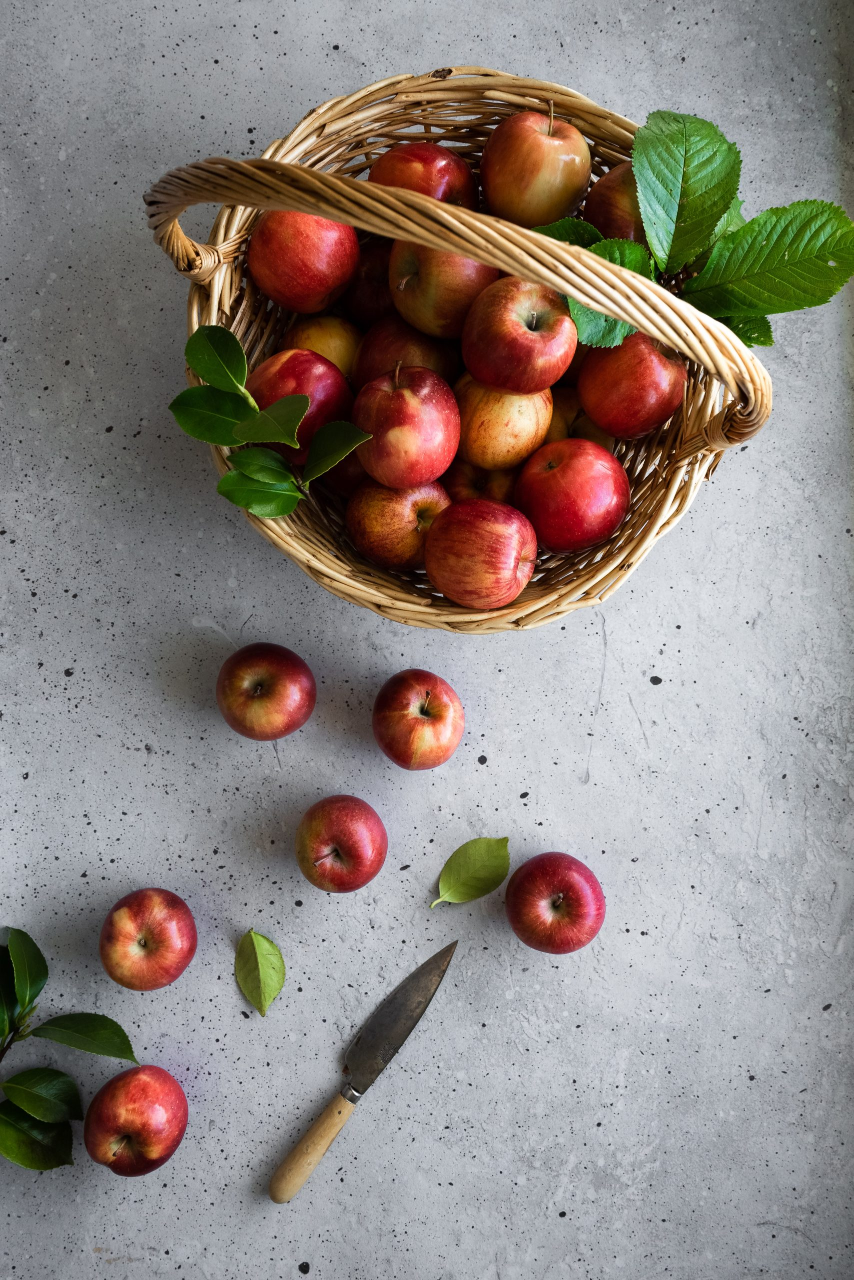overhead image of a basket of red apples with leaves on a grey surface with a paring knife in the bottom middle.