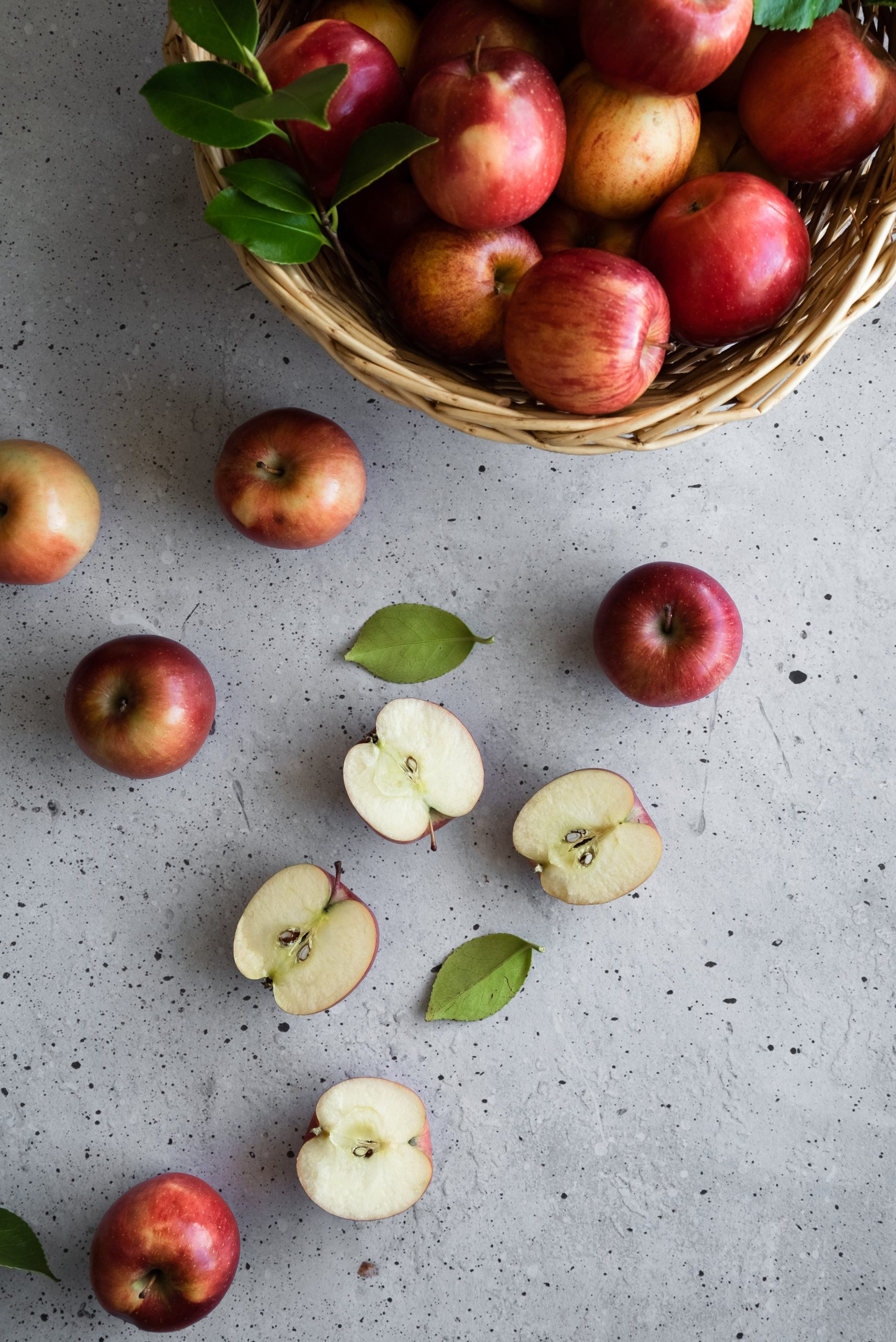 overhead image of a basket of red apples, apple halves and leaves on a grey surface.