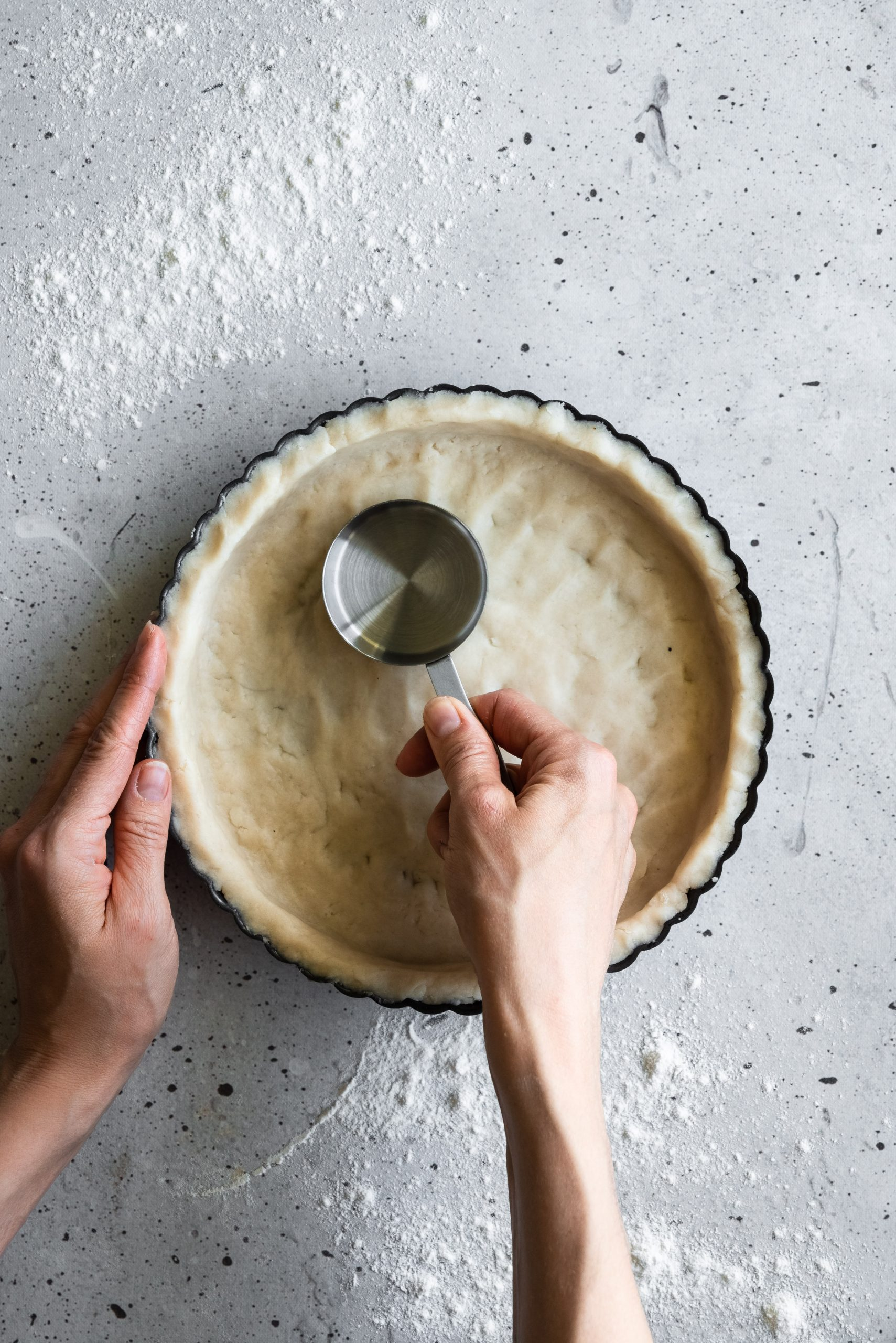 overhead image of two hands pressing tart dough into a tart pan with a small measuring cup.
