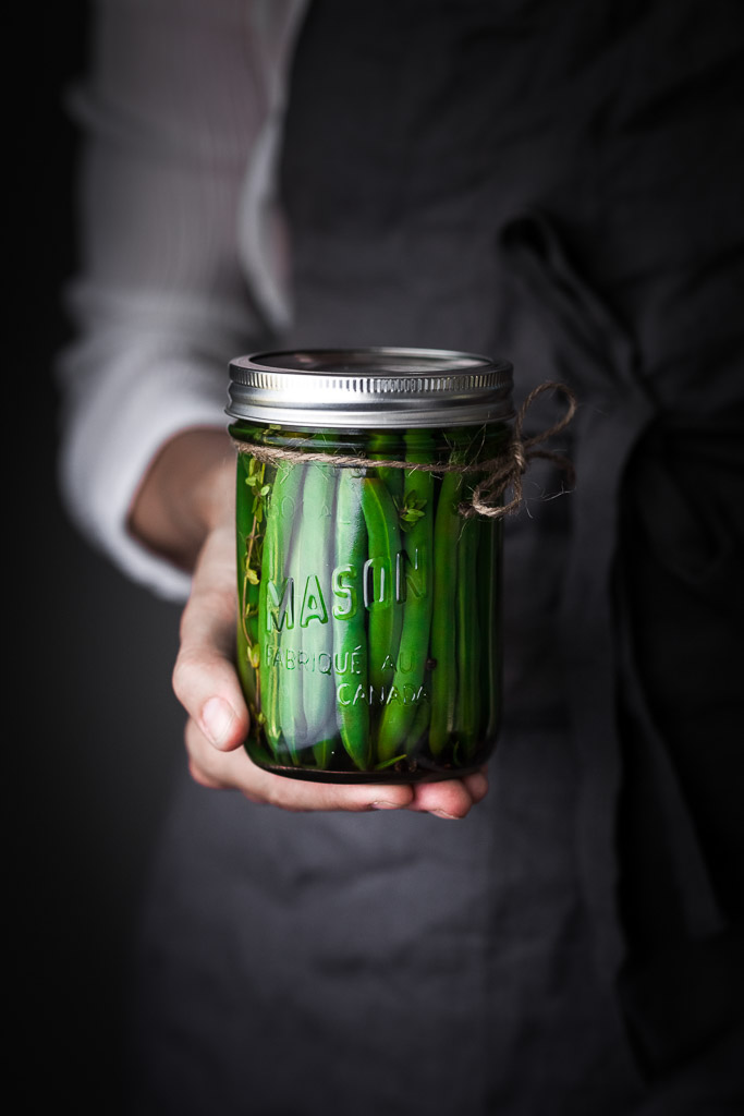A person in a blue apron holding a jar of pickled green beans.