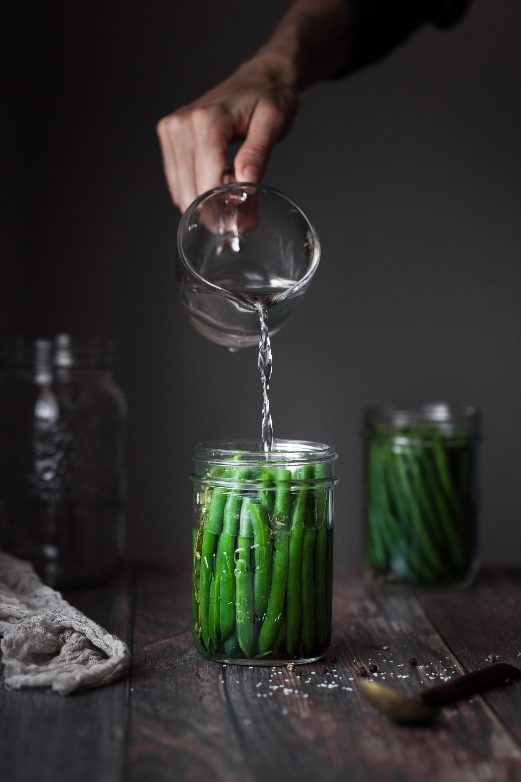 a person pouring brine into a jar filled with green beans.
