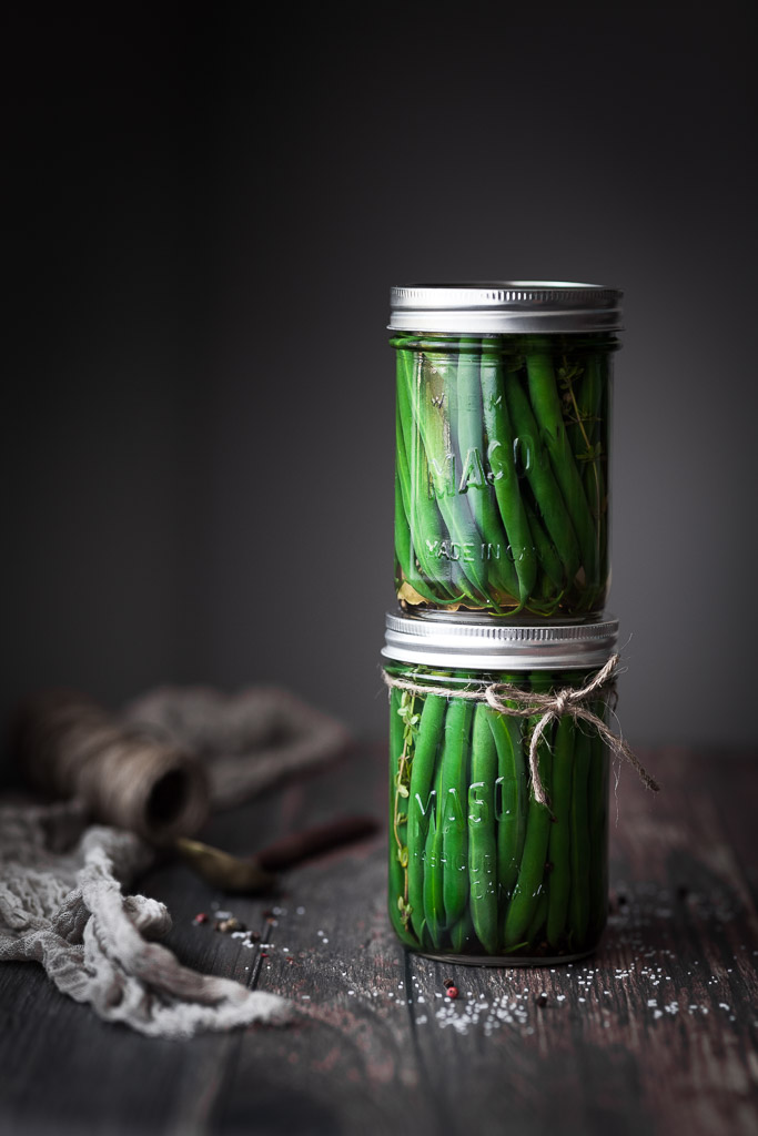 two jars of pickled green beans stacked on top of each other.