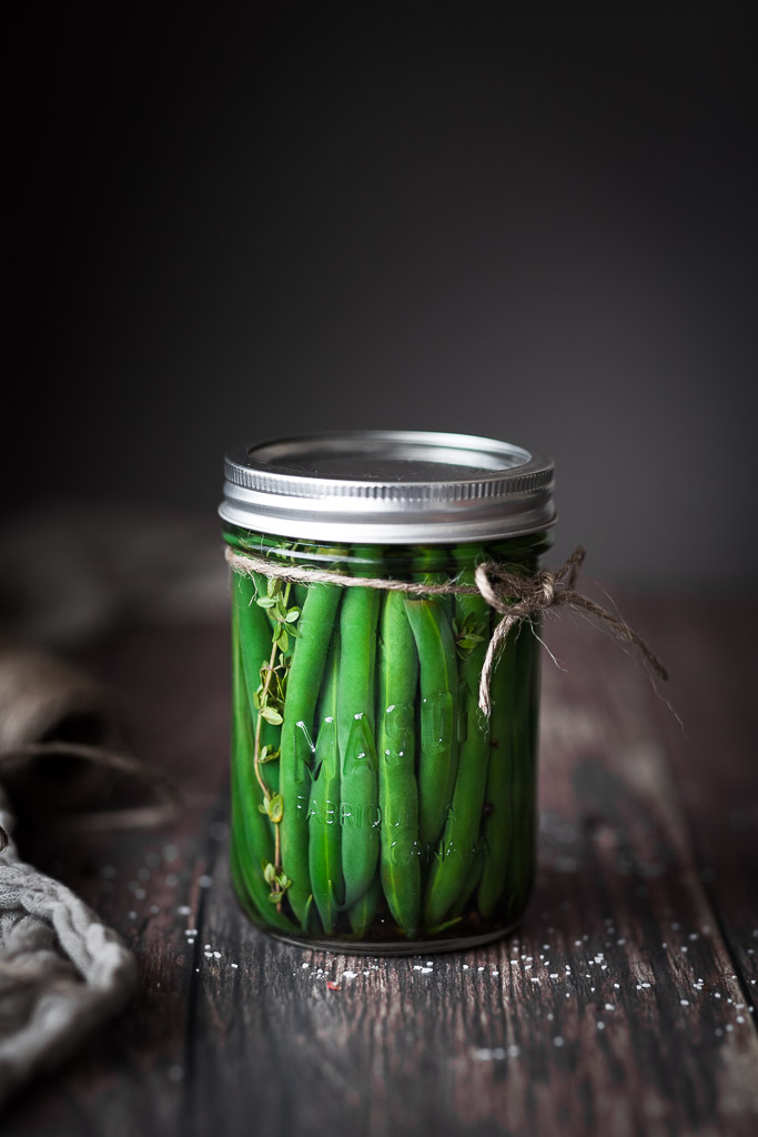 A jar of pickled green beans with twine bow around it.