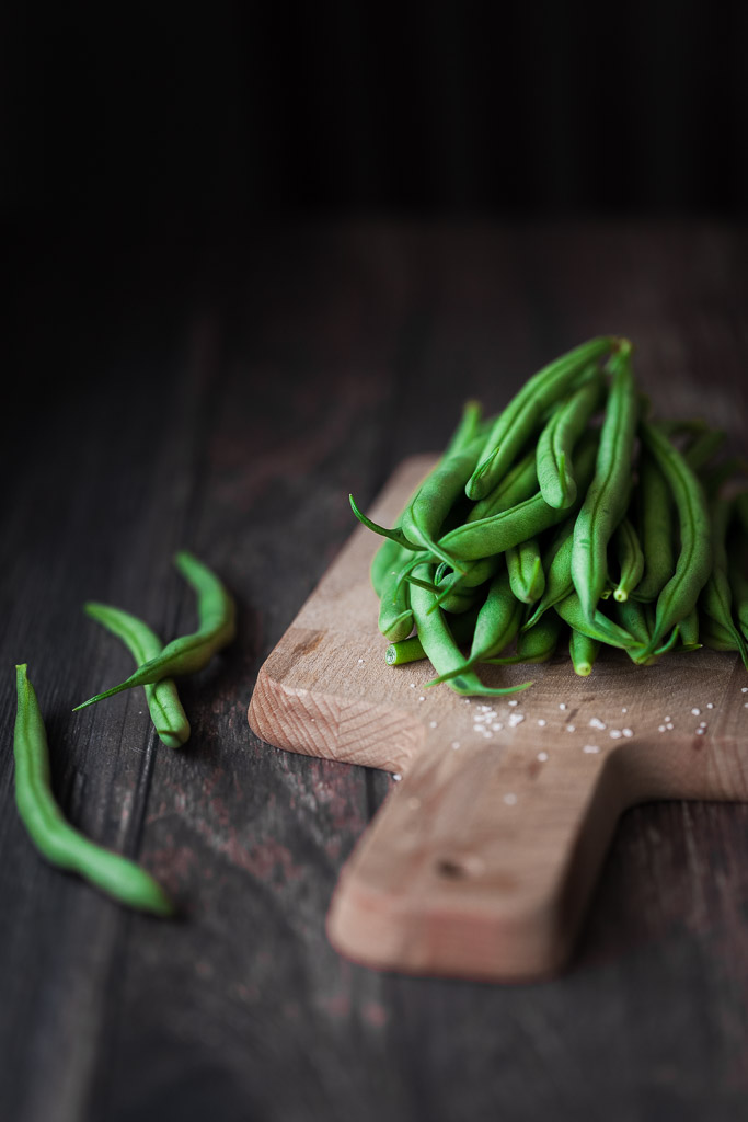 portrait of green beans on a cutting board sittin on a wood surface.