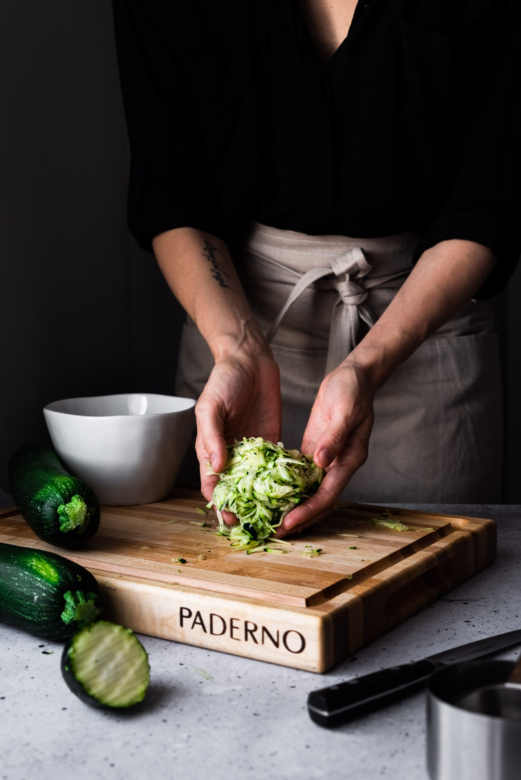A portrait of a person in a beige apron holding shredded zucchini on a cutting board with a white bowl in the background.