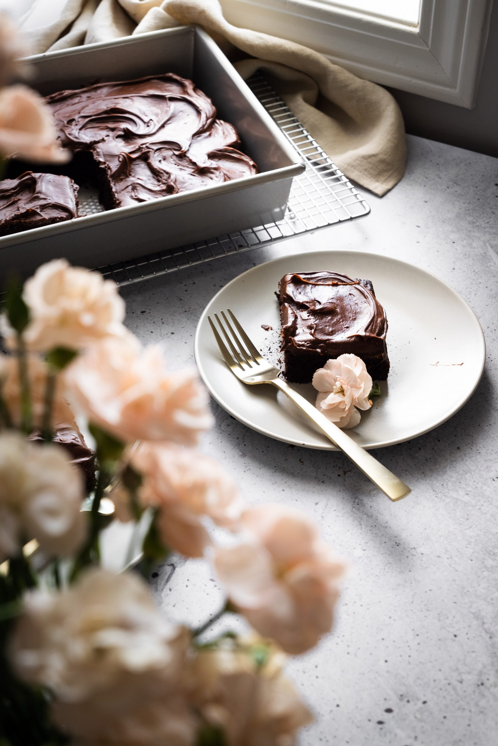 A side view of a slice of chocolate zucchini cake on a white plate with a gold fork and beige flowers in the foreground.