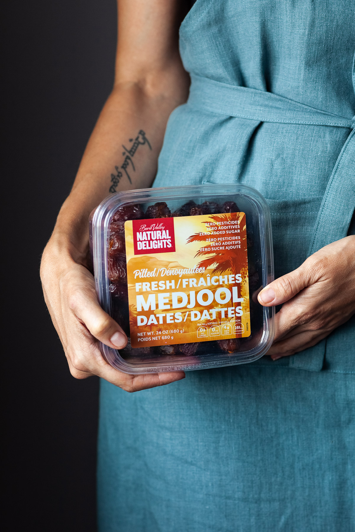 A person in a blue apron holding a box of Medjool dates.