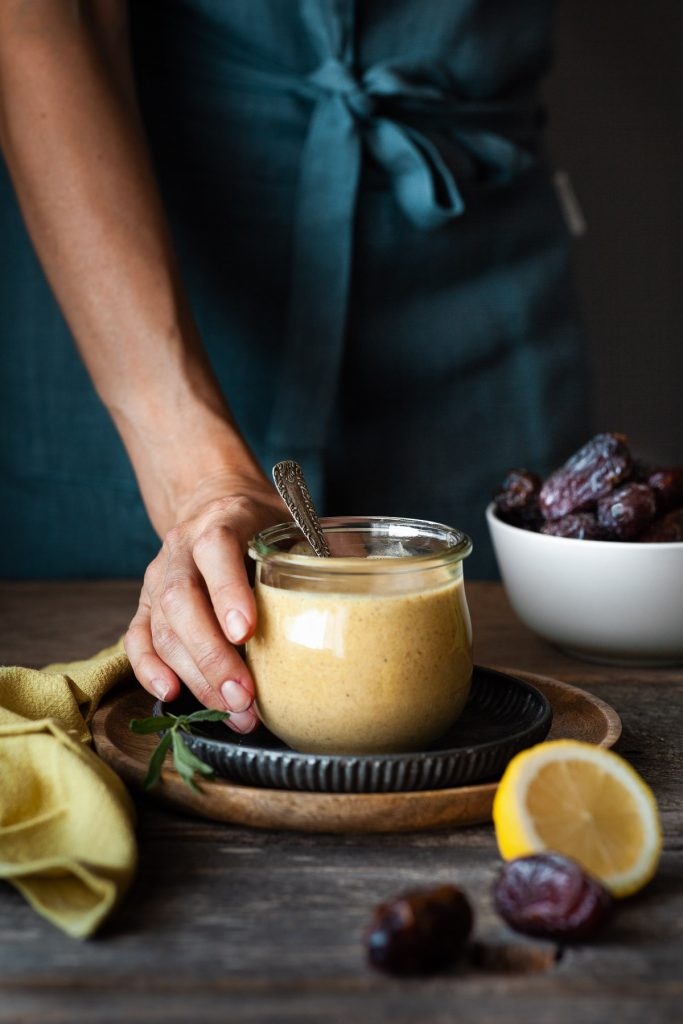 portrait view of a hand holding bowl of dressing with a yellow linen on the side and a bowl of dates in the background.
