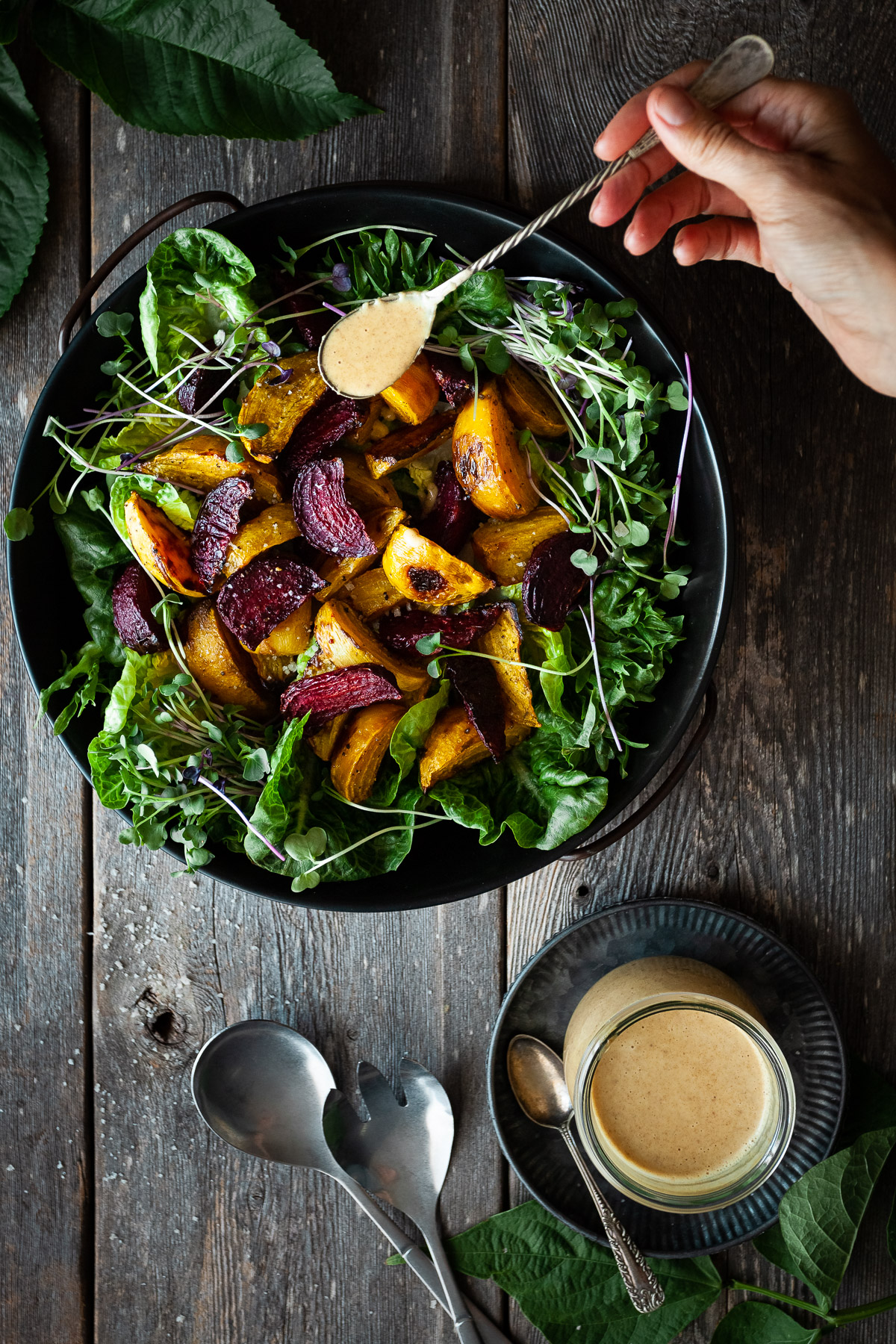 overhead view of a person drizzling dressing on a roasted beet salad on a wood surface.