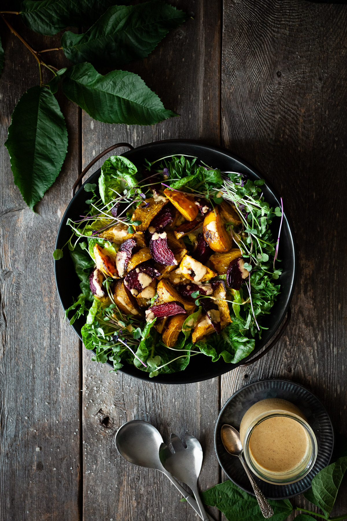 overhead view of roasted beet salad on a wood surface with a bowl of dressing, cutlery.