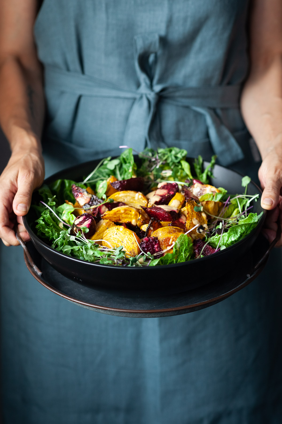 A person in a blue apron holding a bowl of roasted beet salad.