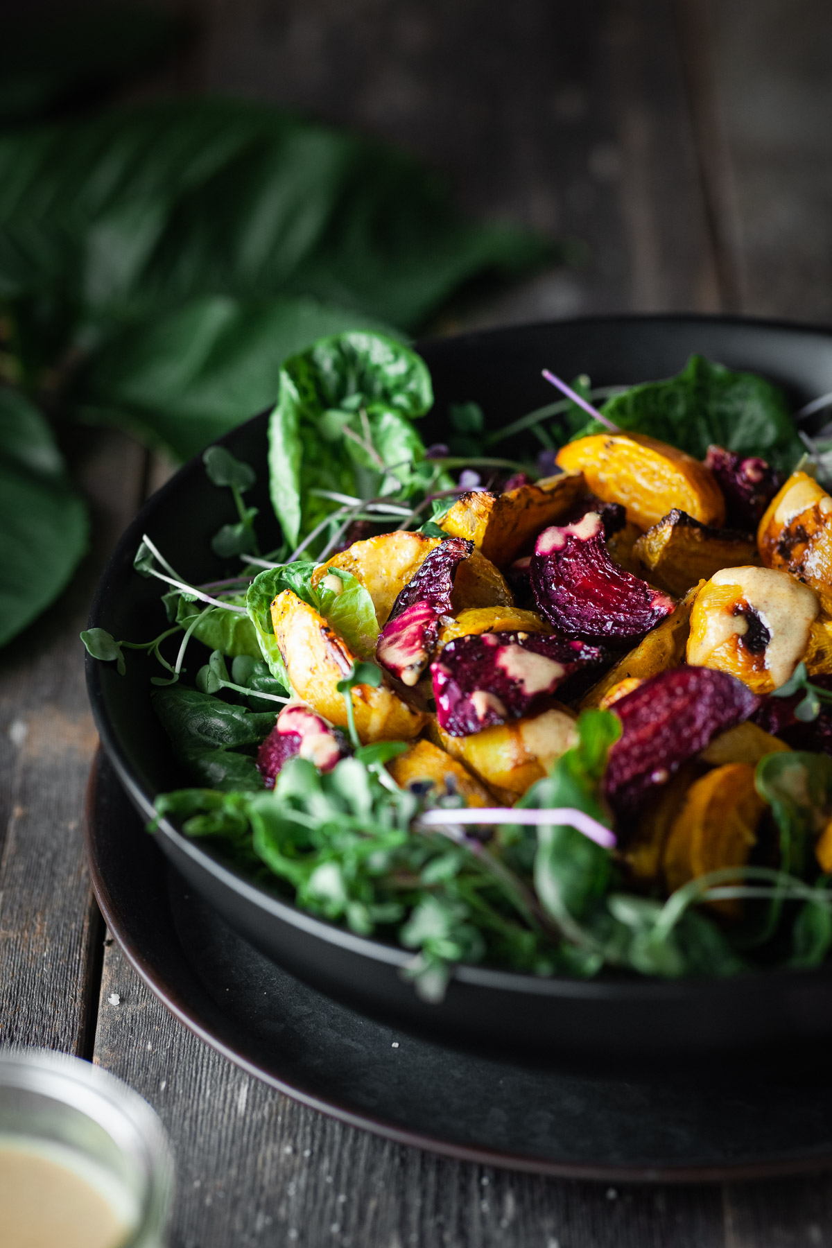 Angled view of roasted beet salad on a wood table.