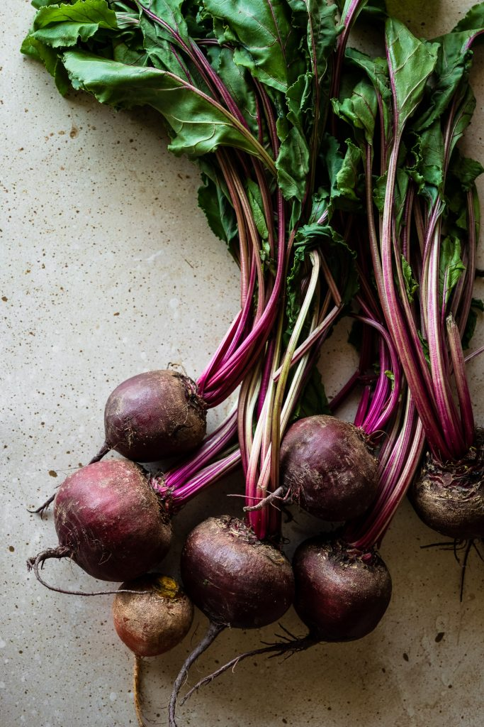 overhead view of whole fresh beets on a stone surface.