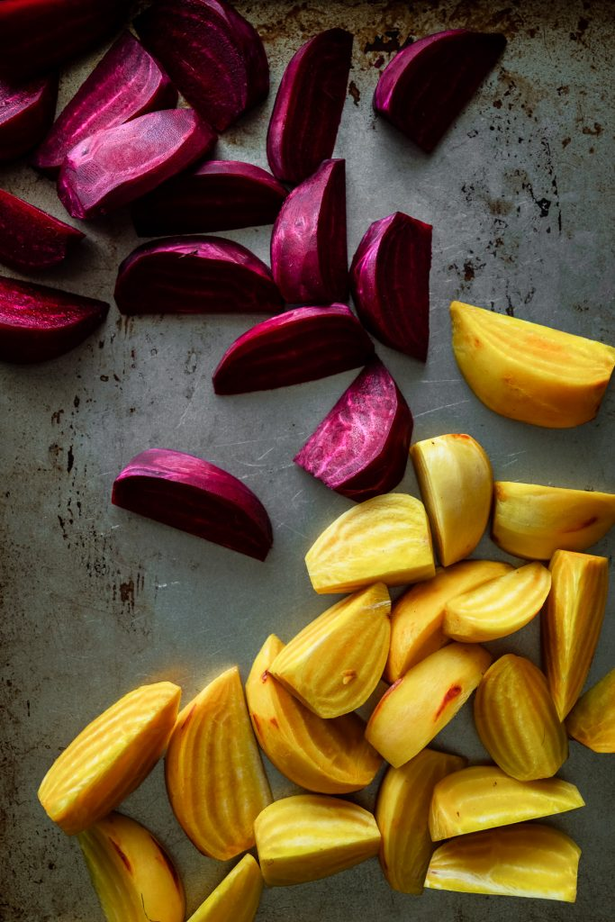 overhead view of sliced purple and gold beet wedges on a baking tray.