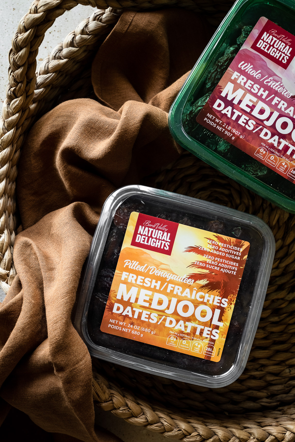 Overhead view of two boxes of Medjool dates in a basket with a brown linen.